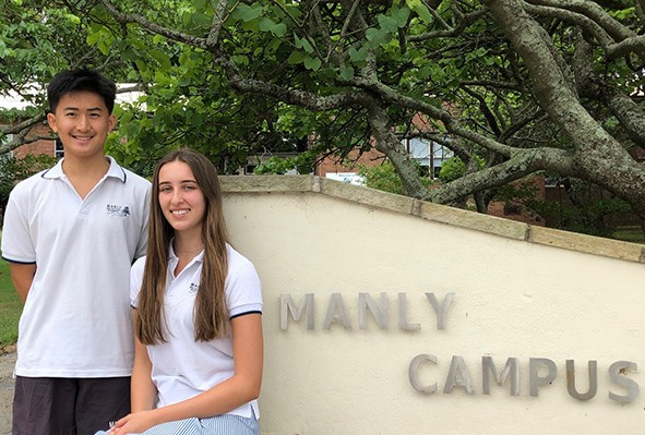 2019 School Captains at the entrance to the school, one sitting and one standing near the Manly Campus name