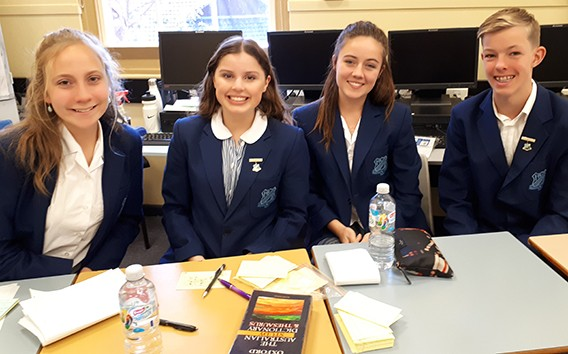 Year 9 debating team sitting at the table with dictionary