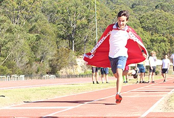 Male student wearing a red cape running on the track at the athletics carnival