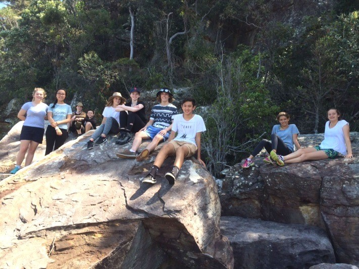 Duke of Edinburgh students sitting on a rock in the middle of the bush