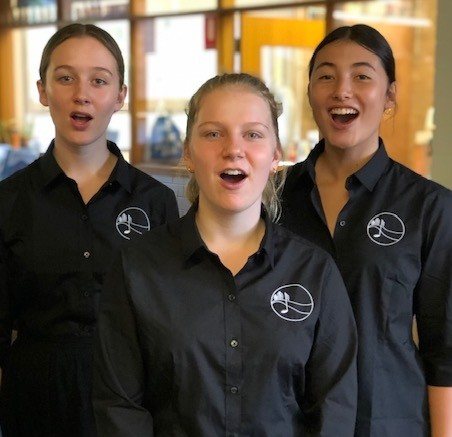 Three female students singing, dressed in black shirts with musical logo