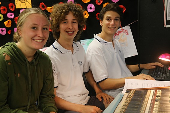 3 students sitting at a keyboard and computer creating music