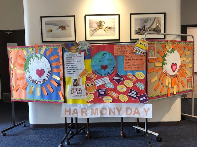 Harmony Day pin board with student messages written on orange paper